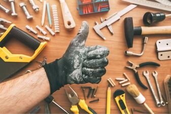 Handyman gesturing a thumbs up above tools that are laid out on the table