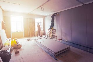 Men installing drywall in an apartment