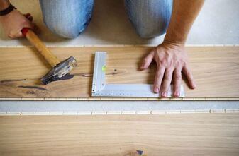 Handyman measuring a wooden floor