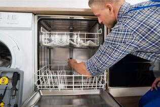 Handyman fixing a dishwasher